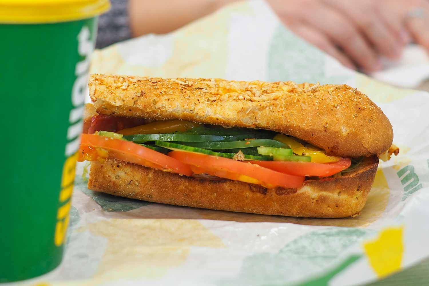 Subway Sandwich with tomatoes and cucumber, laying on wrapper beside a Subway brand cup