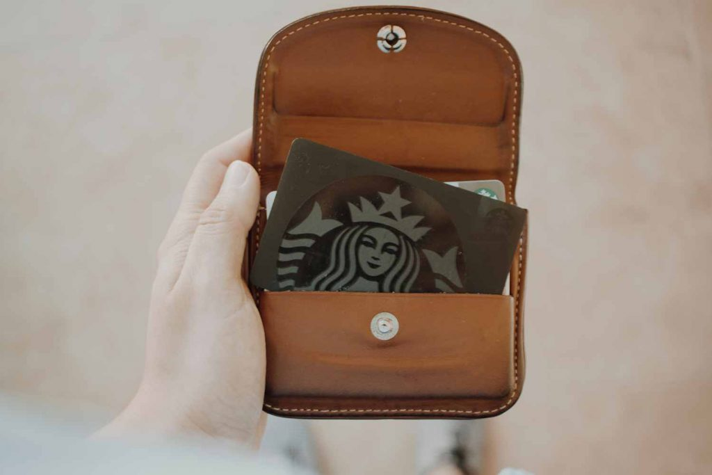 Person holding a black Starbucks card in leather wallet